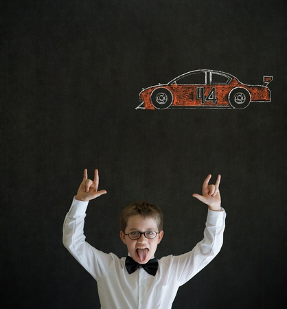 Knowledge rocks boy dressed up as business man with Nascar racing fan car on blackboard background photo
