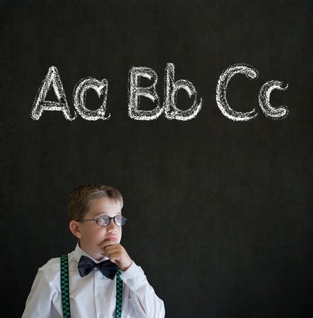 kids writing: Thinking boy dressed up as business man with learn English language alphabet on blackboard background Stock Photo