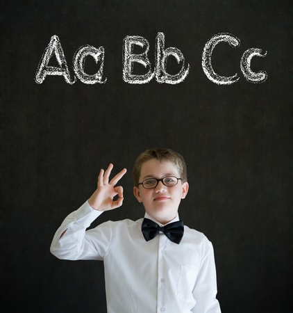 all ok: All ok or okay sign boy dressed up as business man with learn English language alphabet on blackboard background Stock Photo