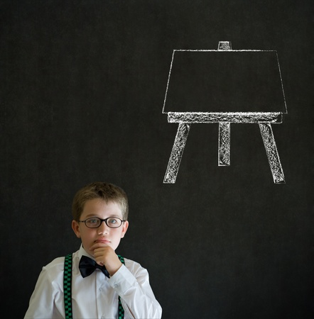 Thinking boy dressed up as business man with learn art chalk easel on blackboard background photo