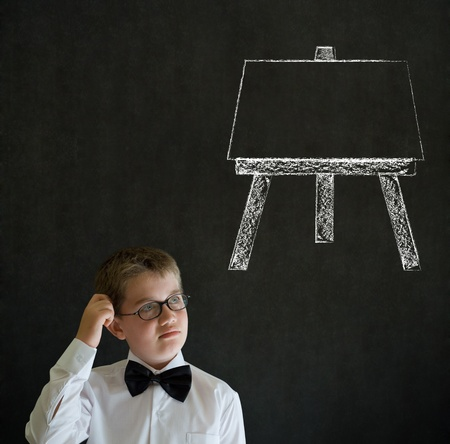 Scratching head thinking boy dressed up as business man with learn art chalk easel on blackboard background photo
