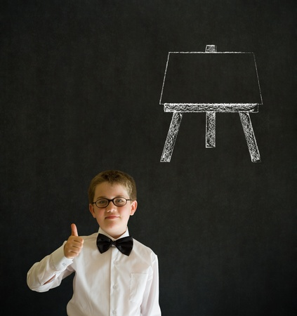 Thumbs up boy dressed up as business man with learn art chalk easel on blackboard background photo