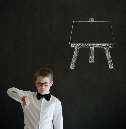 Thumbs down boy dressed up as business man with learn art chalk easel on blackboard background photo