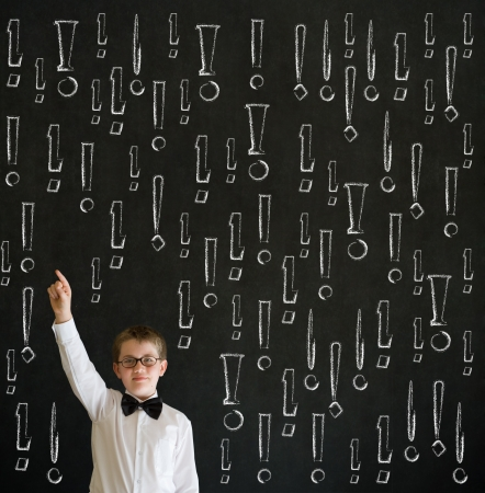 Hand up answer boy dressed up as business man with chalk exclamation marks on blackboard background Stock Photo - 20635906