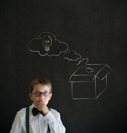 Thinking boy dressed up as business man with chalk thinking out the box concept  on blackboard background photo