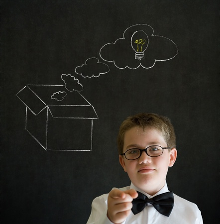 open mind: Education needs you thinking boy dressed up as business man with chalk thinking out the box concept  on blackboard background Stock Photo