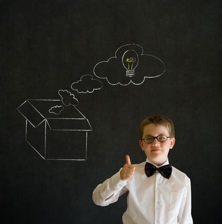 Thumbs up boy dressed up as business man with chalk thinking out the box concept  on blackboard background photo
