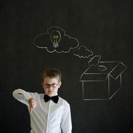 Thumbs down boy dressed up as business man with chalk thinking out the box concept  on blackboard background photo