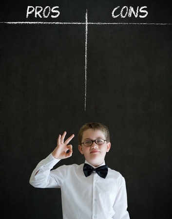 All ok or okay sign boy dressed up as business man with chalk pros and cons decision list on blackboard background Stock Photo - 20618124