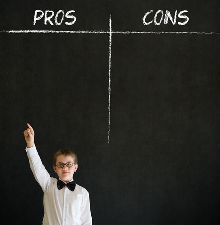 Hand up answer boy dressed up as business man with chalk pros and cons decision list on blackboard background Stock Photo - 20618113