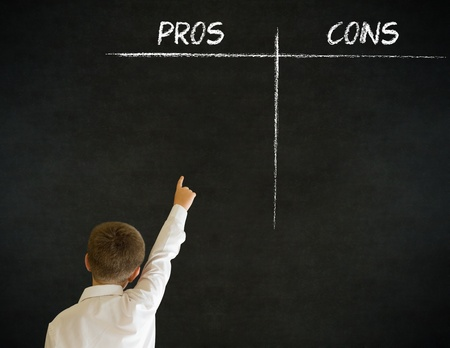 Hand up answer boy dressed up as business man with chalk pros and cons decision list on blackboard background photo