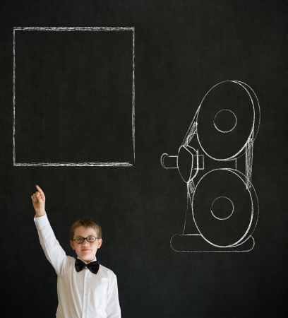 Hand up answer boy dressed up as business man with retro chalk film projector on blackboard background Stock Photo - 20618115