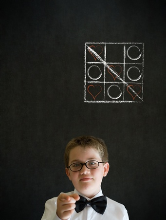 tic tac toe: Education needs you thinking boy dressed up as business man with chalk tic tac toe love valentine concept on blackboard background