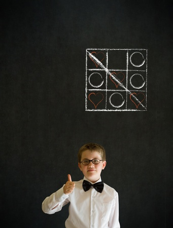 Thumbs up boy dressed up as business man with chalk tic tac toe love valentine concept on blackboard background photo