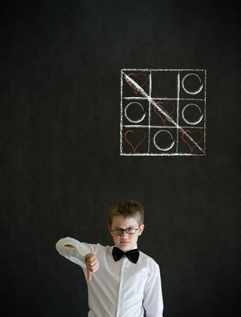 tic tac toe: Thumbs down boy dressed up as business man with chalk tic tac toe love valentine concept on blackboard background Stock Photo