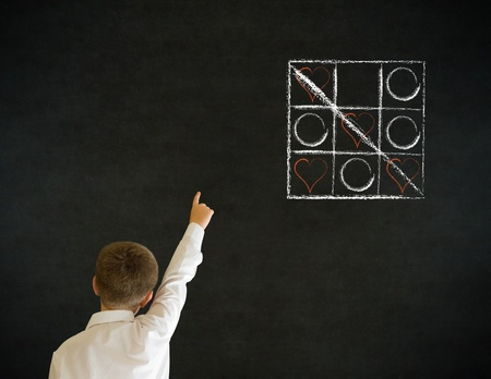 Hand up answer boy dressed up as business man with chalk tic tac toe love valentine concept on blackboard background Stock Photo - 20618131