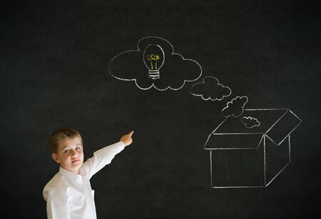 thinking out of the box: Pointing boy dressed up as business man with chalk thinking out the box concept  on blackboard background