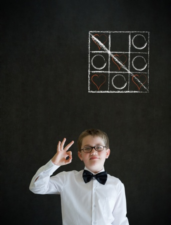 okay sign: All ok or okay sign boy dressed up as business man with chalk tic tac toe love valentine concept on blackboard background Stock Photo