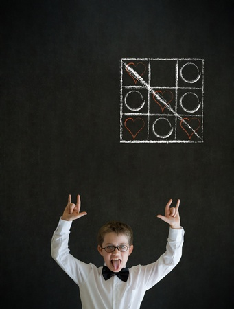 tic tac toe: Knowledge rocks boy dressed up as business man with chalk tic tac toe love valentine concept on blackboard background