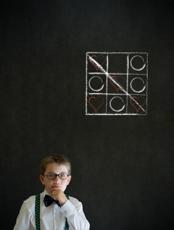 tic tac toe: Thinking boy dressed up as business man with chalk tic tac toe love valentine concept on blackboard background Stock Photo