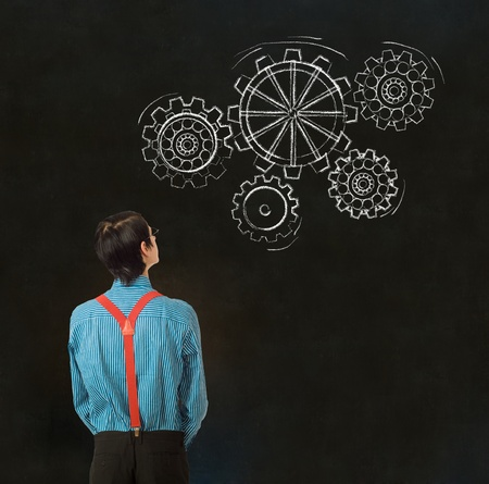 Nerd geek businessman, student or teacher with chalk thinking turning gear cogs or gears on blackboard background photo