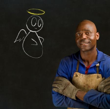 African black man industrial worker with chalk angel on blackboard background photo
