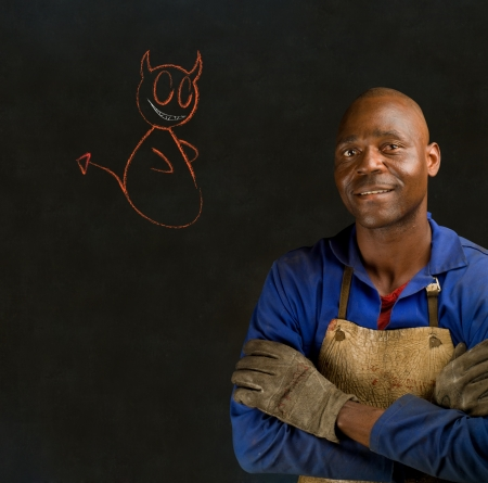 African black man industrial worker with chalk devil on blackboard background photo
