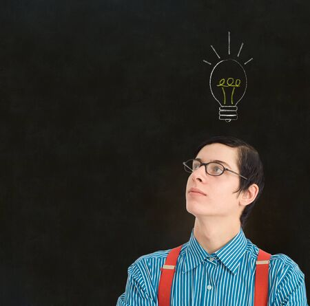 Nerd geek businessman, student or teacher with bright idea chalk thinking lightbulb on blackboard background Stock Photo