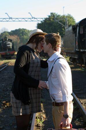 mujer con maleta: Retro hipster pareja romántica de amor en el establecimiento de tren de época