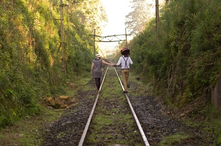 Retro hip hipster romantic love couple walking vintage train tracks photo