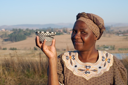 businessowman: Traditional South African Zulu woman basket sales woman selling colourful ethnic baskets made from recycled wire Stock Photo