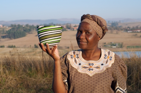africana: Traditional South African Zulu woman basket sales woman selling colourful ethnic baskets made from recycled wire Stock Photo
