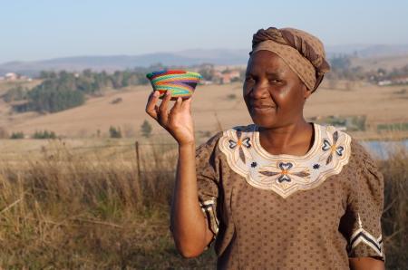 Tradicionales de Sudáfrica Zulu mujer mujer canasta de ventas vendiendo cestas étnicas coloridas hechas de hilo reciclado Foto de archivo