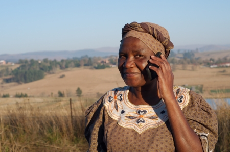 Traditional African Zulu woman speaking on mobile cell phone telephone in rural KwaZulu-Natal  Standard-Bild