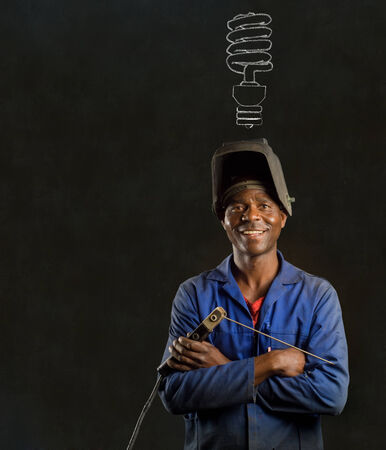 African or American black man industrial worker with chalk energy saving lightbulb on blackboard background photo