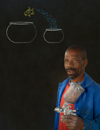 African American black man industrial worker with chalk jumping fish bowls on a blackboard background Stock Photo - 22841946