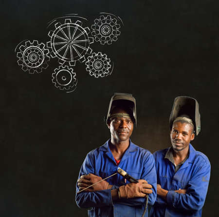 skilled labour: African American black men industrial workers with chalk gears on a blackboard background
