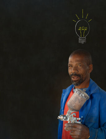 African American black man industrial worker with chalk light bulb on a blackboard background Stock Photo - 22841932
