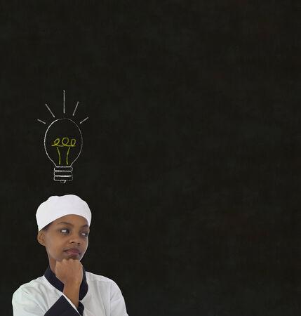 Bright idea lightbulb thinking African or African American woman chef on chalk blackboard background photo