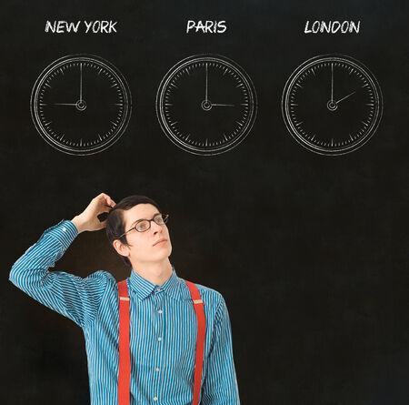 Nerd geek businessman with chalk time difference clocks on blackboard background