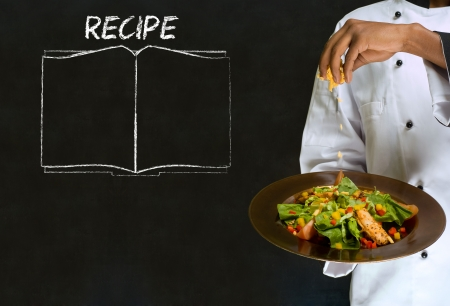 Chef with recipe book on chalk blackboard menu writing background Stock Photo