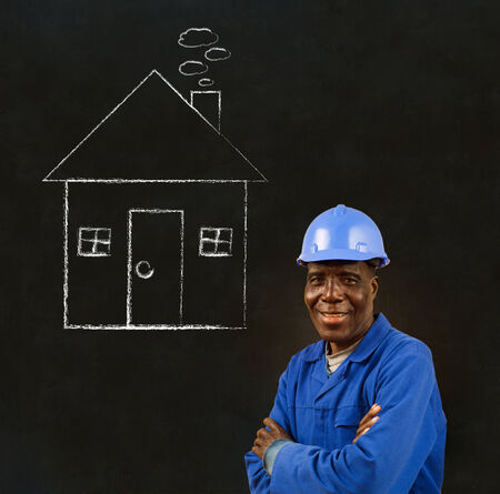 house trained: African American black man worker with chalk house on a blackboard background Stock Photo