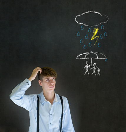Insurance businessman thinking about protecting family from natural disaster on blackboard background photo