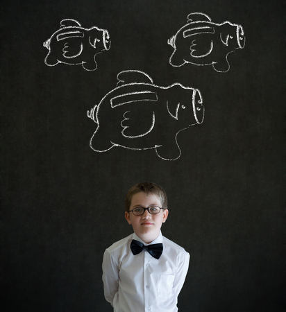 Young business boy with flying money piggy banks in chalk on blackboard background photo