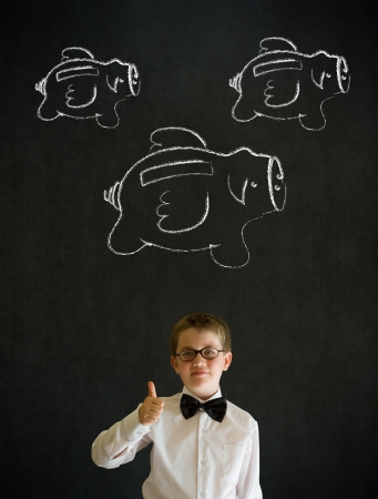 Thumbs up young business boy with flying money piggy banks in chalk on blackboard background photo