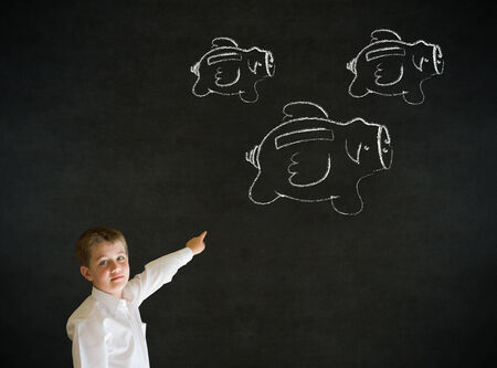 flying money: Young business boy with flying money piggy banks in chalk on blackboard background