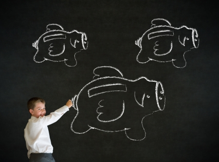 Young business boy drawing flying money piggy banks in chalk on blackboard background photo