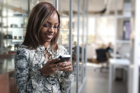 seller: African or black American woman calling or texting on mobile cellphone telephone in office Stock Photo