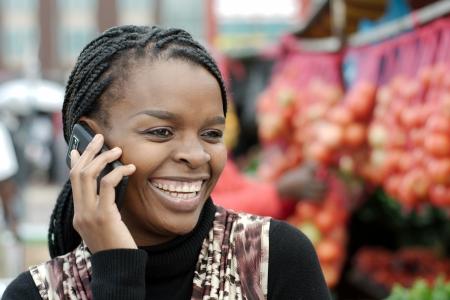 femme africaine: Femme africaine ou noire am�ricaine appelant sur mobile t�l�phone portable dans le township d'Alexandra