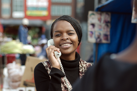 businessowman: African or black American woman calling on landline telephone in Alexandra township